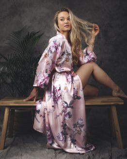 Vrouw zittend op bankje in satijnen kimono met bloemenprint