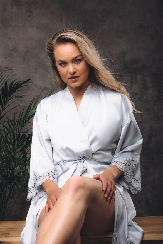 Vrouw zittend op bankje in satijnen kimono met kant en ceintuur