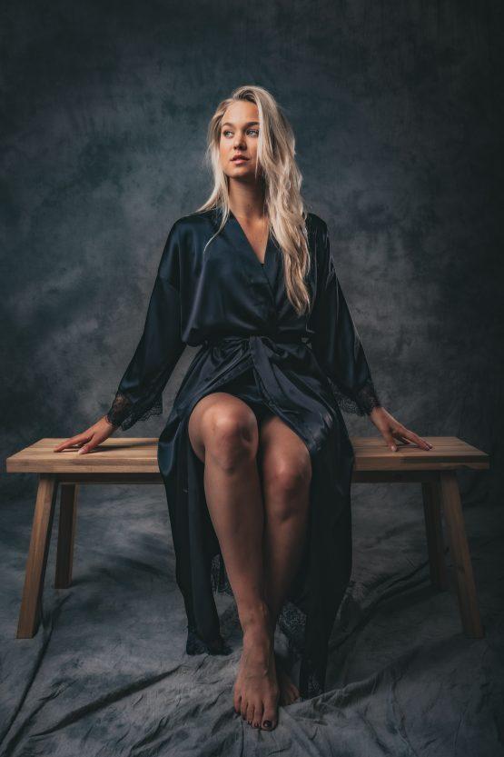 Vrouw in zwarte satijnen kimono zittend op bankje