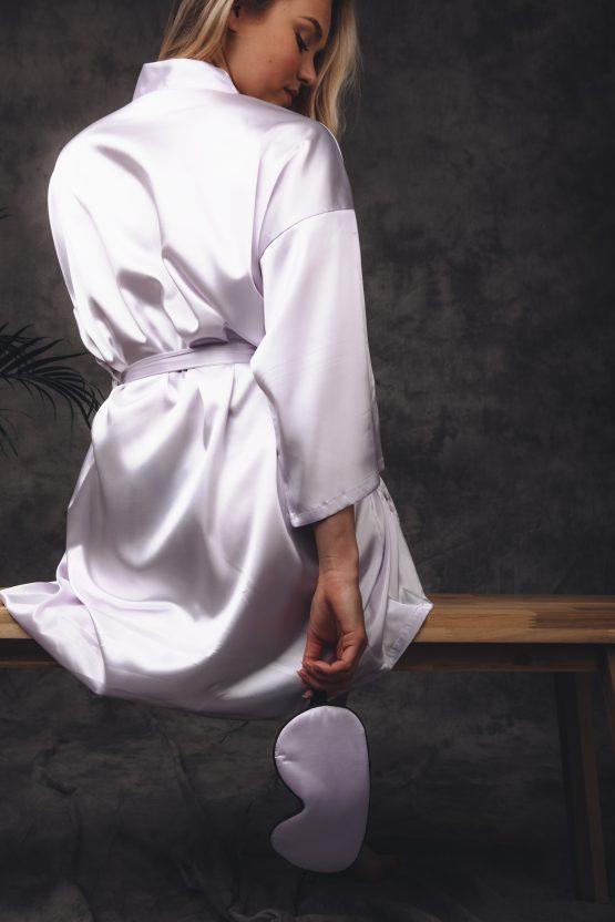 Vrouw zittend in satijnen kimono lila met satijnen slaapmasker in hand