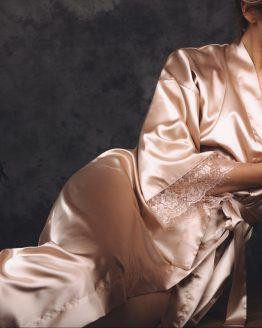 Vrouw liggend op bankje in satijnen kimono van goud met kant
