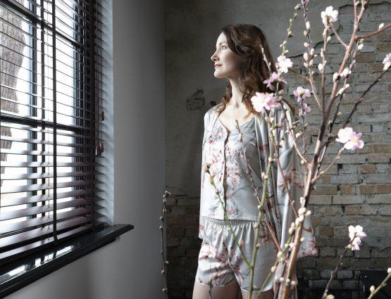 vrouw kijkt uit het raam bij bloesem in pyjama set satijn luxury flower