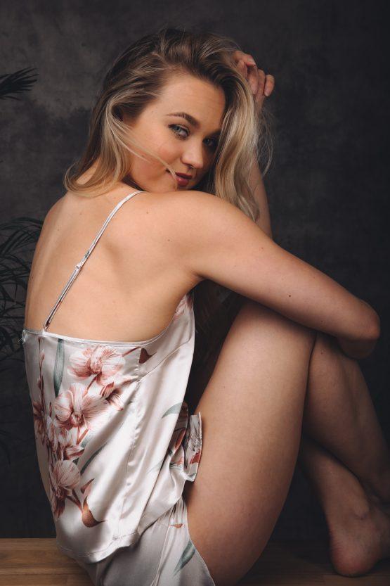 Vrouw zitend op bankje in satijnen pyjama met bloemen