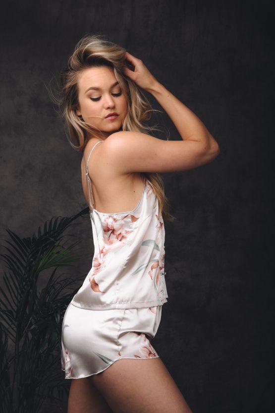 Vrouw met hand in het haar in satijnen pyjama kort met bloemen