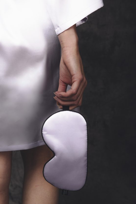 Vrouw met satijnen slaapmasker in haar hand