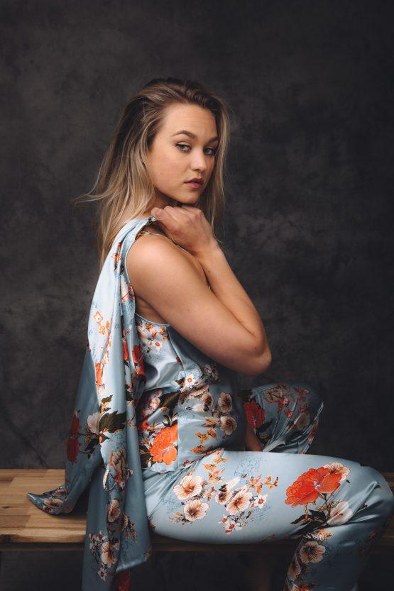 Vrouw in satijnen pyjama zittend op bankje