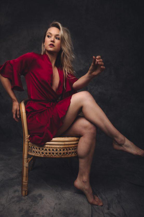 Vrouw zittend in stoel in satijnen kimono rood