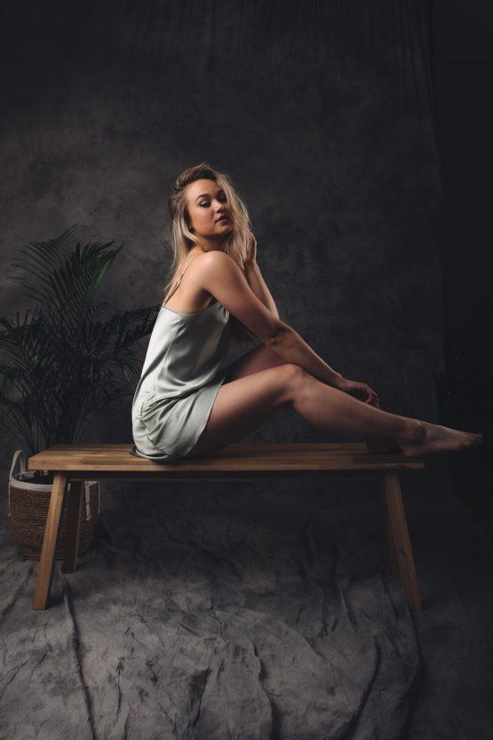 vrouw zittend op bankje in slipdress satijn groen